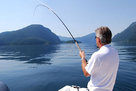 Relaxed man hooking a fish in calm water surrounded by moutains