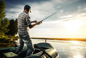 Man in boat reeling in a fish at sunset on the water